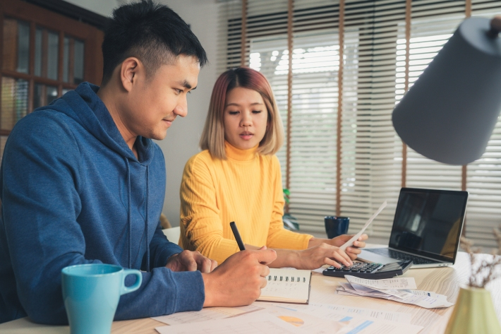Young Asian Couple Managing Finances, Reviewing Their Bank Accou