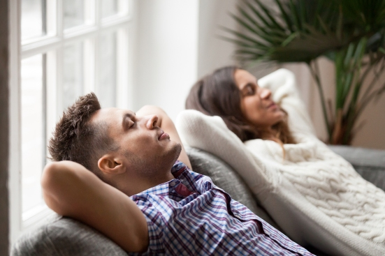 Young Couple Resting On Comfortable Couch Together At Home, Happ