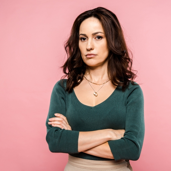 Dissatisfied Woman Standing With Crossed Arms Isolated On Pink