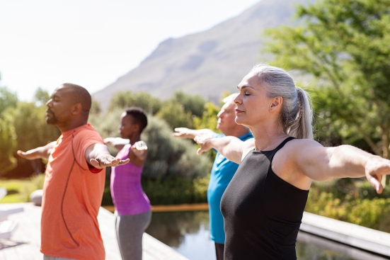 Group of senior people with closed eyes stretching arms outdoor.