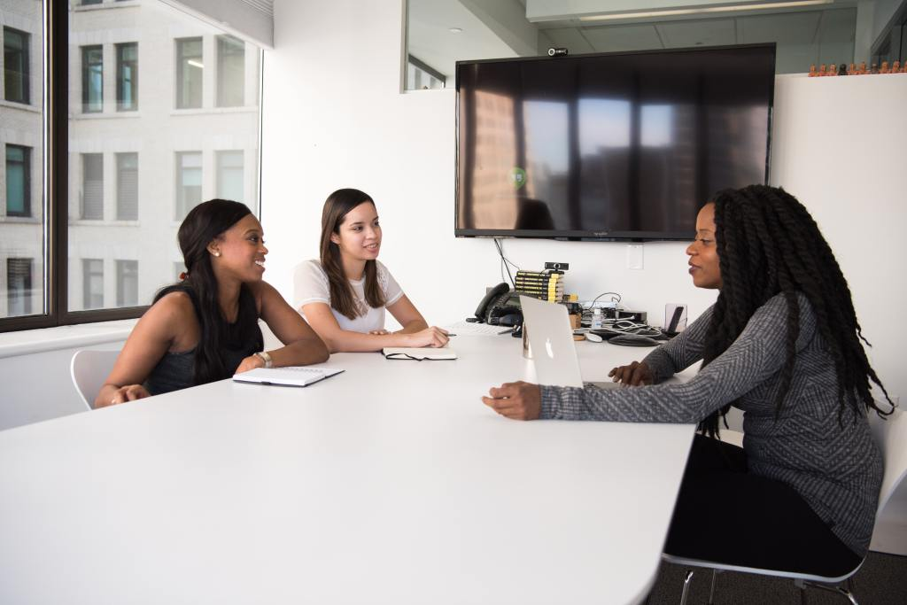 Three women sitting around a conference table talking.