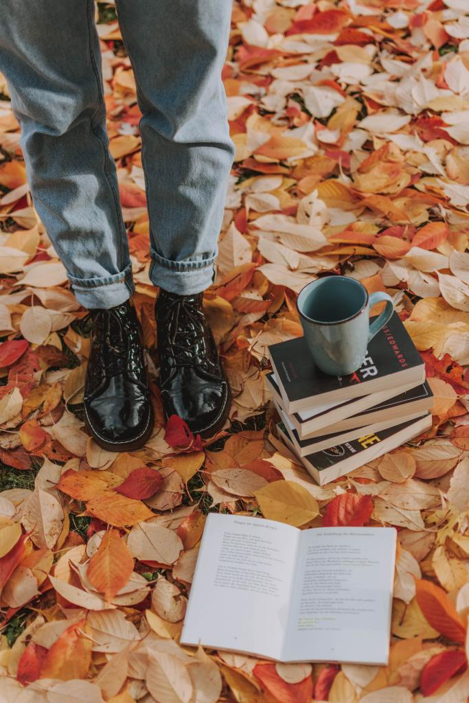 A person standing on fall leaves near a stack of books and a cup of coffee
