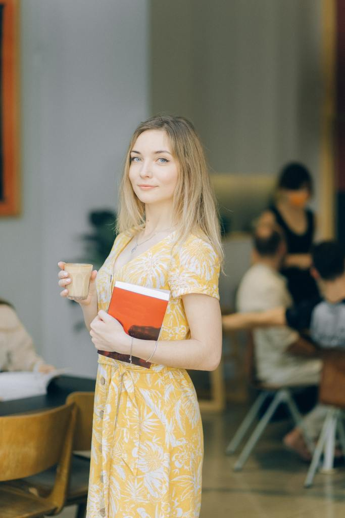 A confident young woman holding a book